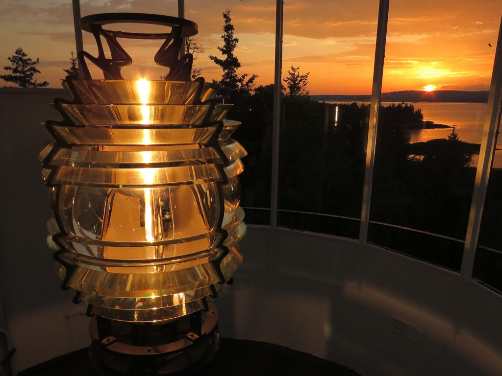 Sunset behind the 4th Order Fresnel lens inside Owls Head Lighthouse